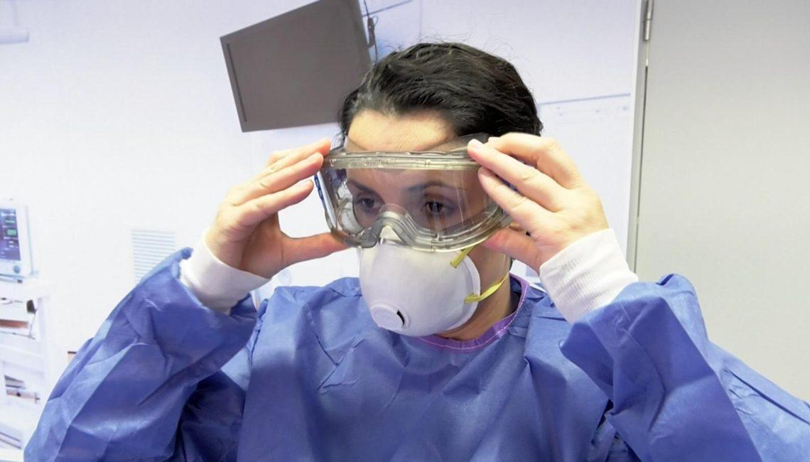 Una enfermera se enfunda el Equipo de Protección Individual contra el COVID 19