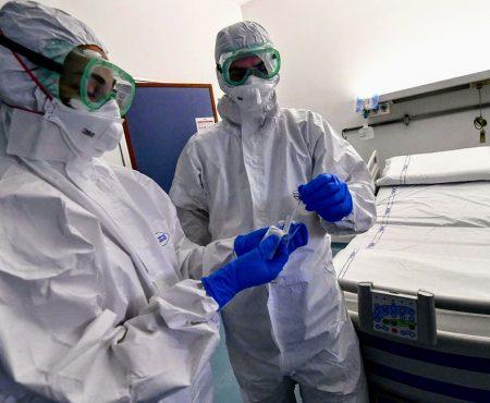 Enfermera y enfermero manejan una prueba de COVID-19