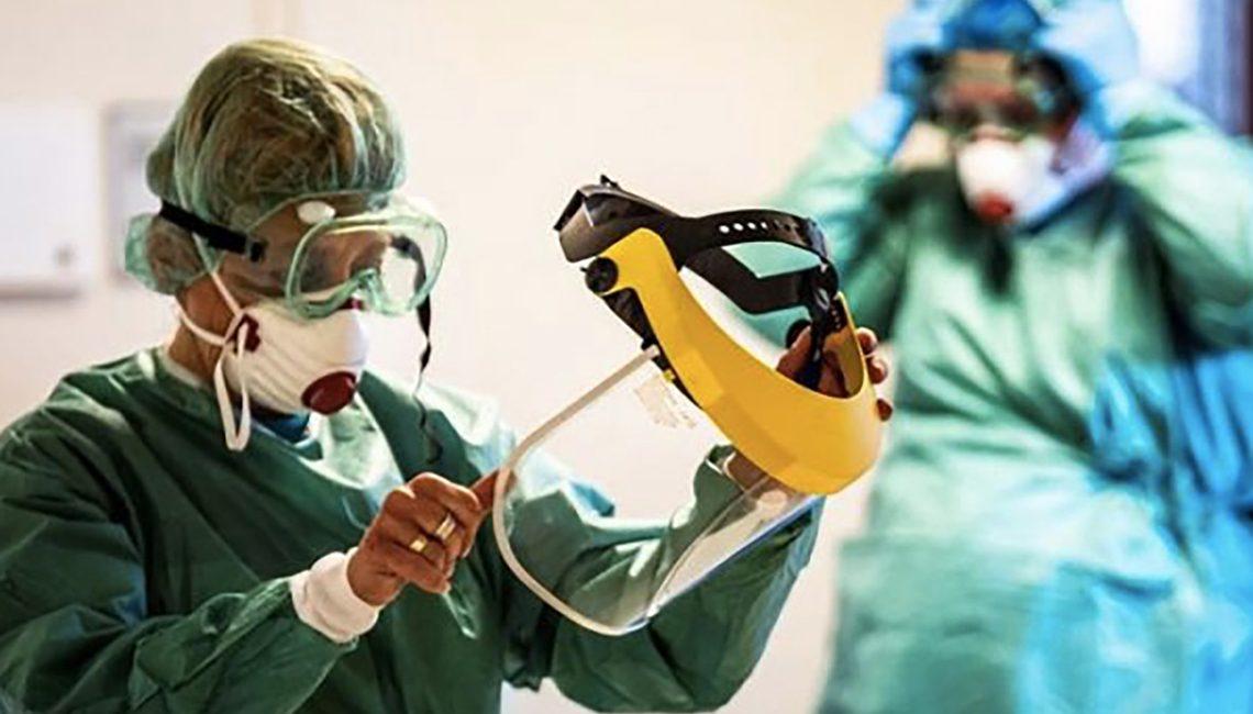 Enfermera se pone la pantalla de protección contra COVID 19