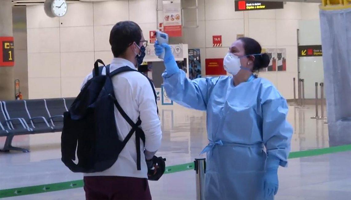 Enfermera en aeropuerto efectúa un control de toma de temperaturas a los pasajeros de un vuelo internacional