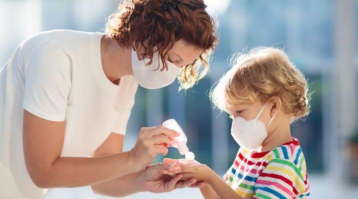 Enfermera escolar enseña a un niño cómo limpiar sus manos con un gel hidroalcohólico