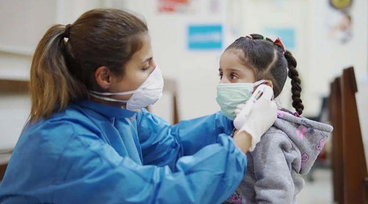 Enfermera escolar toma la temperatura de una niña con mascarilla contra el COVID 19