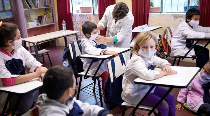 Enfermera escolar coloca adecuadamente la mascarilla a un niño en un colegio
