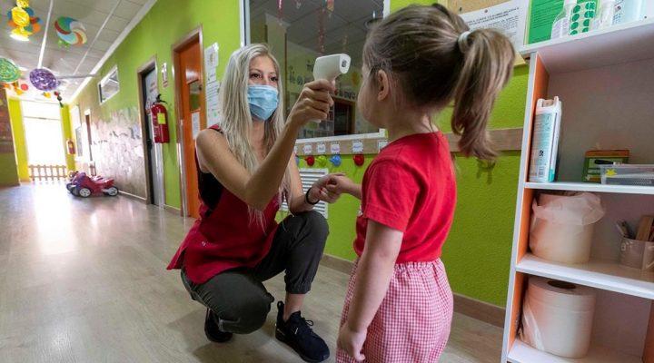 Mujer toma la temperatura de una niña en una escuela infantil en plena crisis del COVID 19