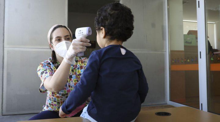 Enfermera toma la temperatura de una niña en plena crisis del COVID 19