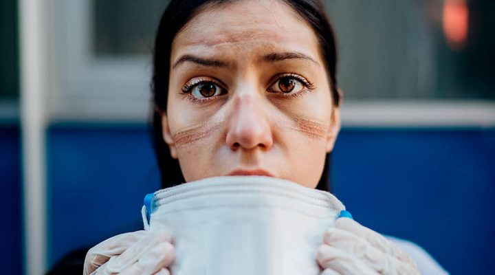Una enfermera muestra las marcas de la mascarilla en su rostro en plena crisis del COVID